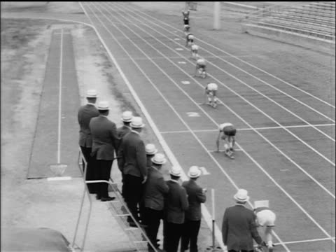 B/W 1965 high angle REAR VIEW runners in relay race taking off / documentary