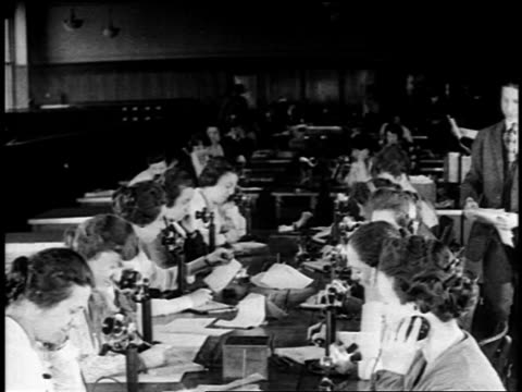 B/W 1919 high angle row of women at long table answering telephones / newsreel