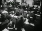 B/W 1939 high angle rows of women using adding machines at desks in office / documentary
