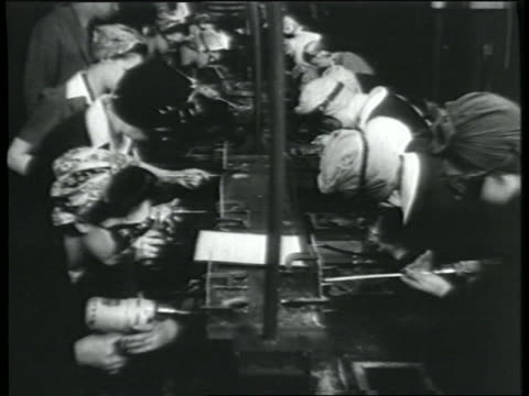 B/W 1943 high angle rows of women using power tools in bomber factory