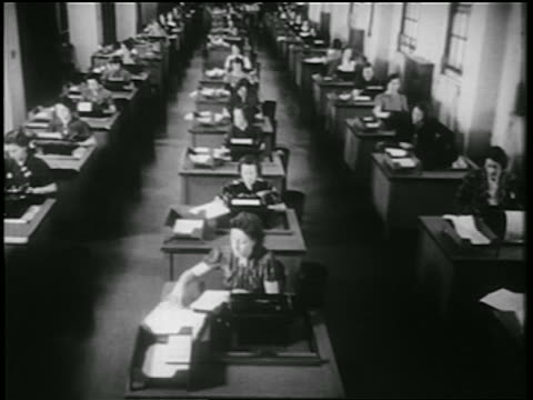 B/W 1939 high angle rows of women using typewriters at desks in office / documentary