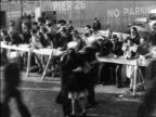 B/W 1945 high angle sailor woman hugging as others pass by / WW II homecoming / documentary