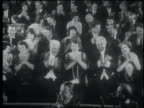 B/W 1922 high angle seated audience in formalwear clapping
