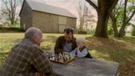High angle senior man playing chess against mature man and young boy outdoors / autumn