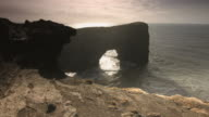 High angle shot of a stone arch on the coast of southern Iceland.