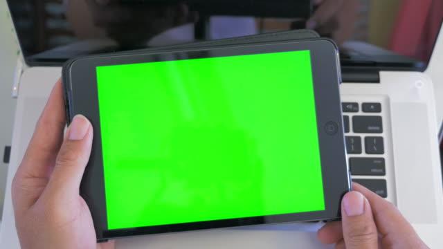 Alto angolo colpo di uomo utilizzando talea digitale, schermo verde