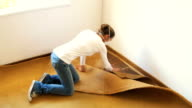 High angle shot of woman renovator pulling out old carpet