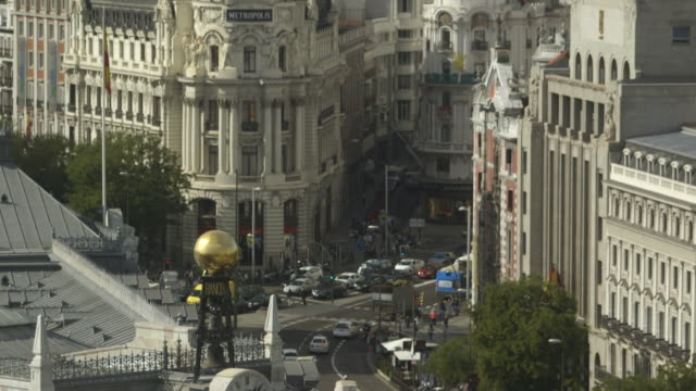 High angle shot panning up to a building with a gilded dome, Madrid.