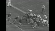 LS high angle shots of kickoff beginning ArmyNavy football game Municipal Stadium / MS Army quarterback Arnold Tucker tackled / WS crowd cheers in...