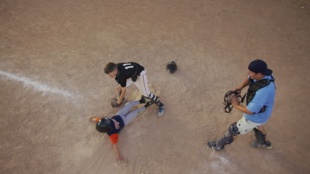 High angle slow motion medium shot of baseball player sliding to home plate / American Fork, Utah, United States