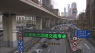 High Angle static , Traffic information and warnings display on a digital sign above a highway near a downtown area. / China