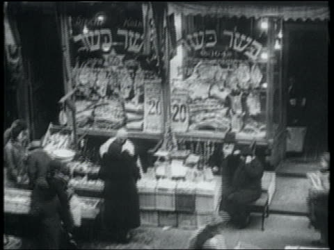 B/W 1932 high angle street vendors outside store with Hebrew writing on windows / Lower East Side, NYC