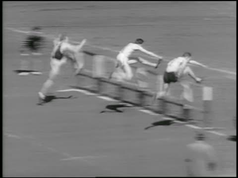 B/W 1934 high angle PAN three men jumping hurdles in relay race / Philadelphia / newsreel