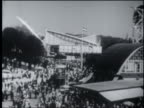 B/W 1958 high angle tilt up PAN cable cars moving above crowded Brussels World's Fair