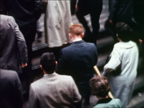 1960 high angle tilt up crowd walking up stairs of subway station to sidewalk / bus in background / NYC / newsreel