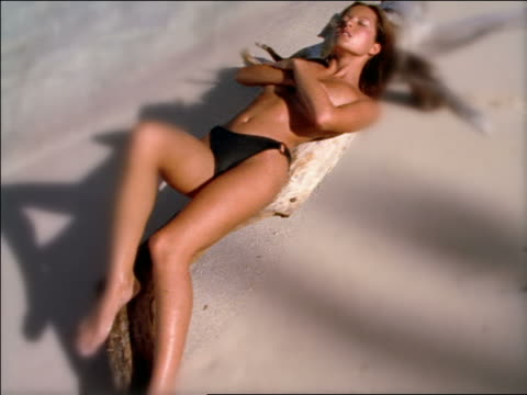 SELECTIVE FOCUS high angle tilt up topless woman lying on large piece of driftwood on beach tanning / Seychelles