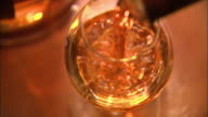 High Angle tilt-down - A bar patron picks up a wineglass partially filled with whiskey. / Scotland, Great Britain, UK
