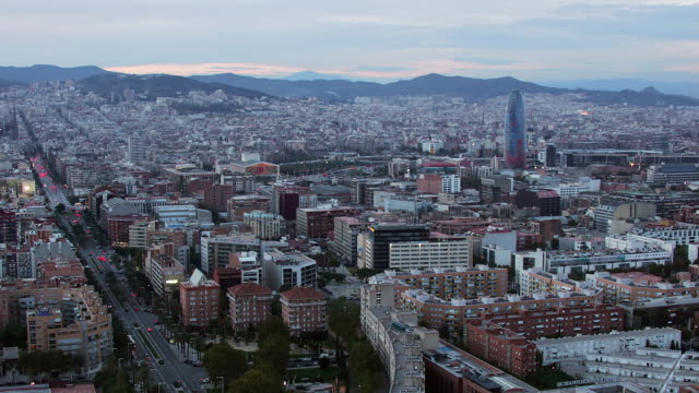 High angle time lapse wide shot skyline with Torre Agbar from day to night/ Barcelona