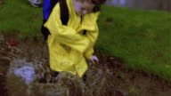 high angle MS tracking shot young boy running + jumping in puddle with older children watching