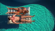 High angle two men laying on rafts w/arms locked in swimming pool