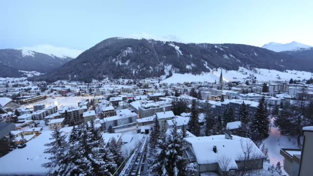 High angle view dusk falling over Davos Alpine ski resort ahead of the World Economic Forum 2013 mountains and snow as night falls filmed from...