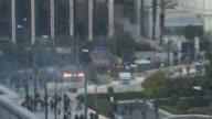 High angle view Greek Parliament building Mount Lycabettus PAN to protesters in square smoke from tear gas / High angle view riots flames and smoke...