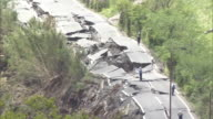 High angle view of a huge crack in a road in Mashiki Town after intense earthquakes jolted Kumamoto Repair workers investigating the site Zooming in...