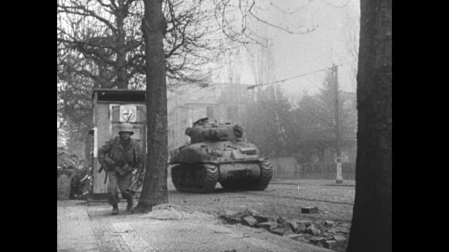 High angle view of double line of American 3rd Army soldiers on a dirt road / sign 'FrankfurtM 8 km' / smoke rises over city / VS American soldiers...