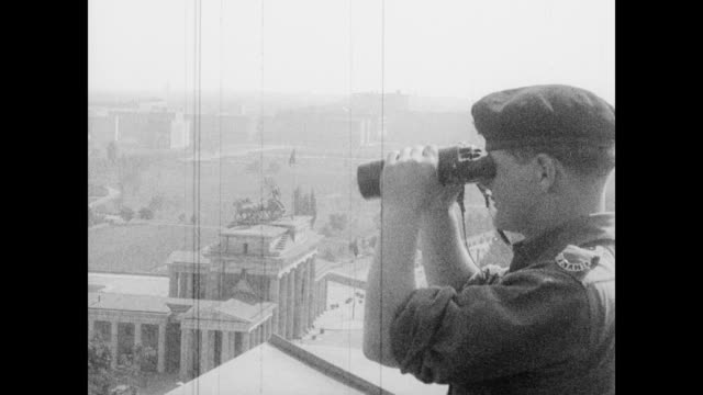 / High angle view of soldiers guarding the Brandenburg Gate / French soldier looks through binoculars / aerial of Reichstag Berlin Wall Brandenburg...