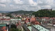 High angle view of the city skyline in Ljubljana from office buildings to old town and castle High angle view old town and castle pull out to...
