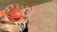 High angle view over basketball hoop of young women playing basketball / woman making layup