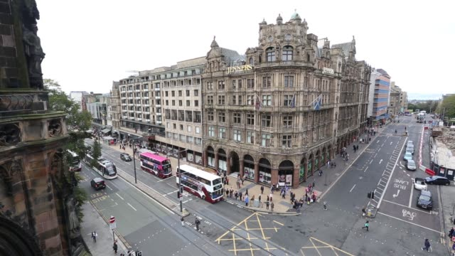 High angle view shoppers and vehicles pass along Princes Street in Edinburgh UK on Saturday Sept 20 High angle view a tram passes Jenners department...