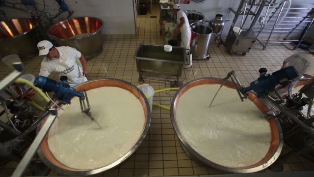 High angle views machinery stirs milk in copper vats during the Parmigiano Reggiano cheese manufacturing process at Coduro cheesemakers in Fidenza...
