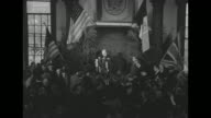 LS high angle views of crowded room as Former British Prime Minister Winston Churchill takes podium and gives twofinger victory sign US British and...