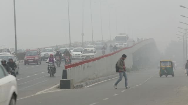 High angle views traffic moves along a road shrouded in haze in New Delhi India on Monday Jan 20 Vehicles move in heavy traffic along a road shrouded...