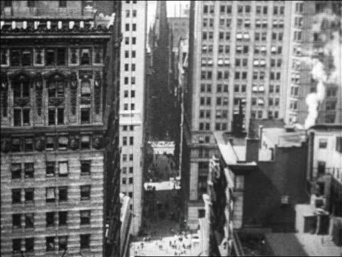 B/W 1929 high angle Wall Street with Trinity Church in background / NYC / newsreel