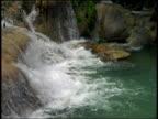 high angle waterfall going over rocks into pool / Jamaica