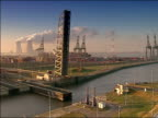 High angle wide shot Berendrecht Lock closing at Port of Antwerp with Doel Nuclear Power Station on horizon/ Antwerp, Belgium