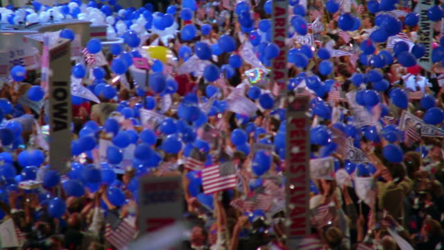 high angle wide shot PAN blue balloons falling on state delegates on floor of Democratic National Convention / low angle