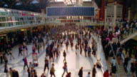 High angle wide shot camera turning with crowd of commuters walking in Liverpool Street Station / London