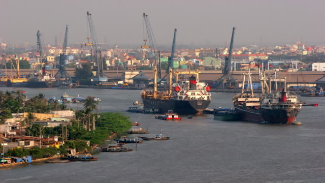 High angle wide shot cargo ship and smaller boats float in Saigon River with cranes in background / Ho Chi Minh City, Vietnam