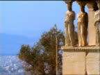 high angle wide shot PAN cityscape to Caryatids statues supporting Erechtheion temple / Acropolis / Athens, Greece