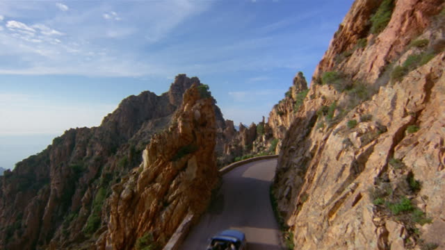 High angle wide shot convertible driving down winding mountain road/ Corsica