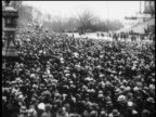 B/W 1929 high angle wide shot PAN crowd gathered in rain at Hoover's presidential inauguration / newsreel