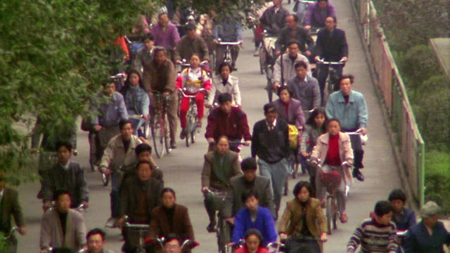 High angle wide shot crowd of Chinese people riding bicycles on road towards camera / Chengdu, China