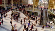 High angle wide shot crowd of commuters using stairs and escalators at Liverpool Street Station / London, England