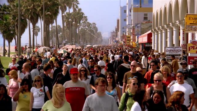 High angle wide shot crowd walking on promenade at Venice Beach / Venice, Los Angeles, California