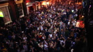 High angle wide shot crowds of people celebrating Mardi Gras on Bourbon Street at night / New Orleans, Louisiana