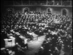 B/W 1945 high angle wide shot FDR sits at desk surrounded by congressmen in last address to Congress / Capitol Bldg