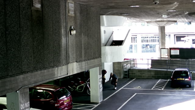 High angle wide shot freerunners jumping off stairs in parking garage